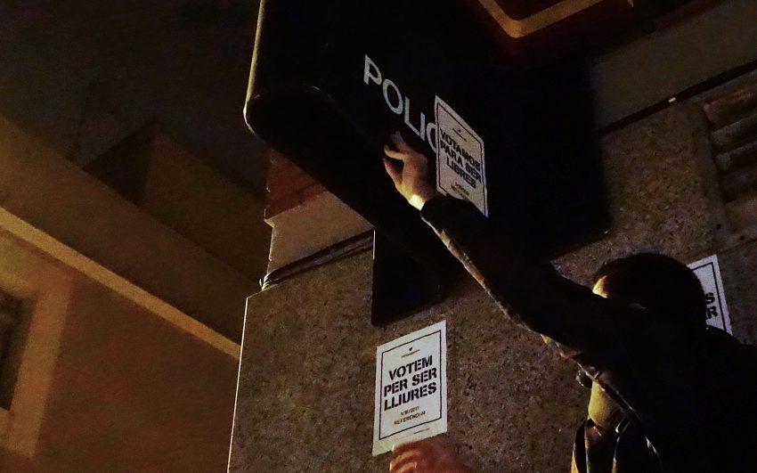 Un sediciós demòcrata enganxa un cartell al logo de la Policía Nacional / DGM