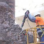 Un operari enderroca el mur hidràluic del segle XVIII DGM